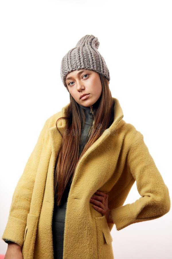 Modello castana della donna dei pantaloni a vita bassa alla moda in soprabito beige alla moda e cappello grigio fotografia stock