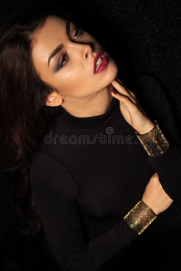 Modello castana sexy con le grandi labbra e posin rosa dei brasoletes dell'oro immagini stock