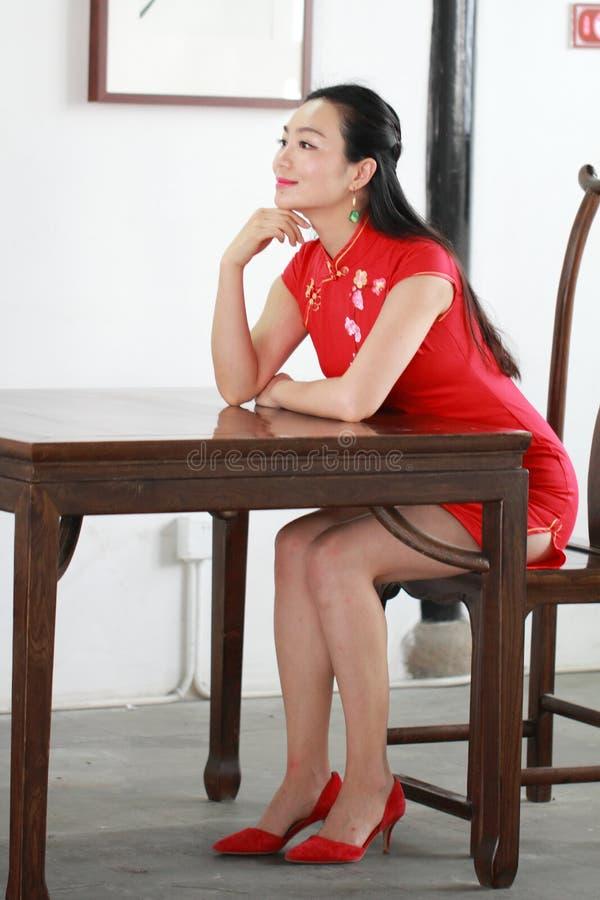 Modello cinese Sit del cheongsam su un panchetto fotografia stock libera da diritti