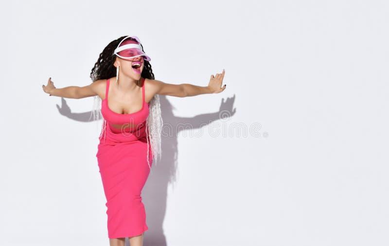 Modello con blocchi In parasole, in top rosa e in gonna Urlare, spalmare le braccia, leggermente appoggiato Posa isolata in bianc fotografie stock