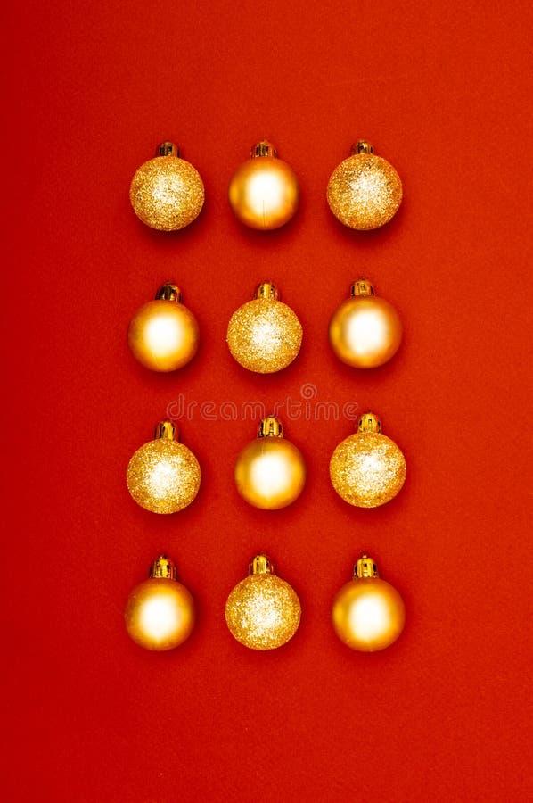 Modello creativo della decorazione di Natale delle bagattelle multiple dell'oro con i precedenti rossi fotografia stock libera da diritti