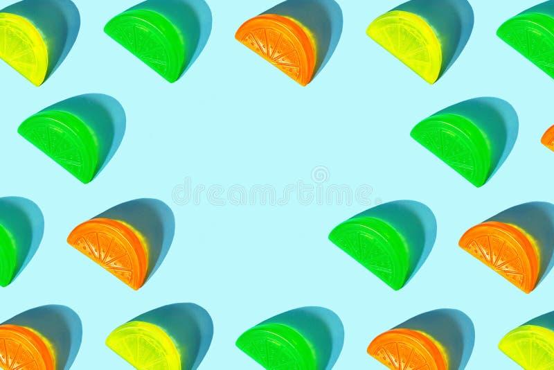 Modello creativo delle fette variopinte dell'agrume come ghiaccio per il cocktail su fondo blu pastello fotografia stock