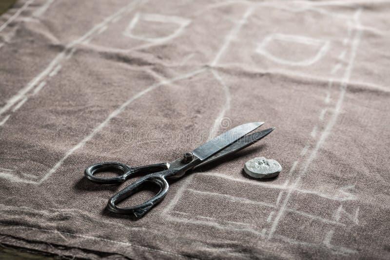 Modello d'annata del sarto dei pantaloni con le forbici ed il panno immagini stock