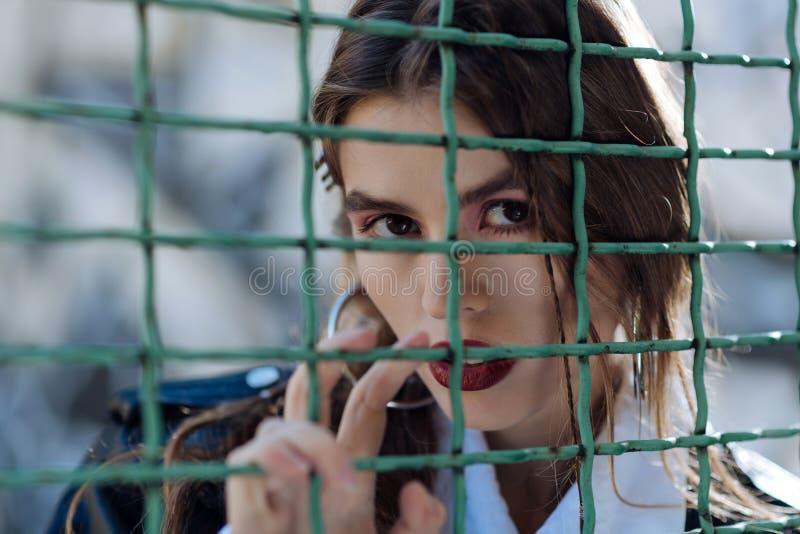Modello dagli occhi scuri della foto con le labbra rosse che posano per la rivista di stile della via fotografie stock