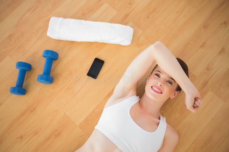 Modello dai capelli di marrone stanco di misura in abiti sportivi che si rilassano dopo lo sport fotografia stock