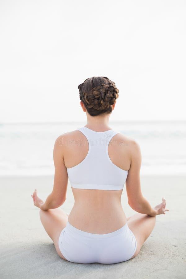 Modello dai capelli marrone esile attraente in abiti sportivi bianchi che meditano nella posizione di loto fotografia stock