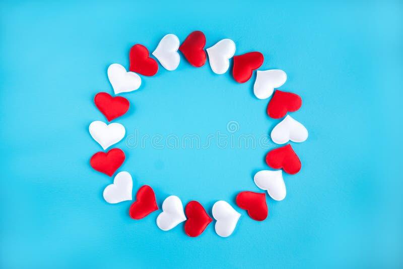 Modello dei cuori rossi e bianchi su un fondo blu Concetto per il giorno del ` s del biglietto di S. Valentino immagini stock