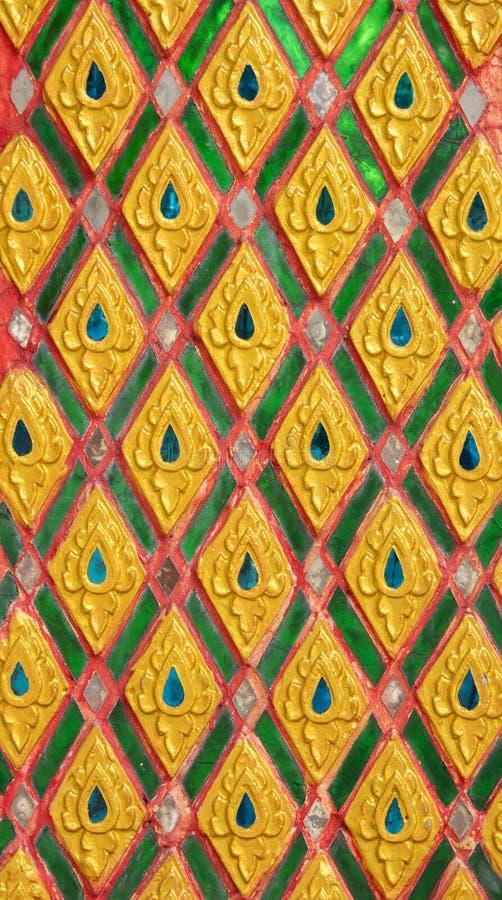 Modello del fiore dell'oro scolpito su progettazione dello stucco della parete indigena immagini stock libere da diritti