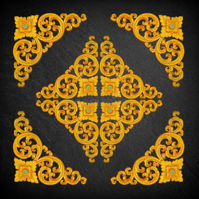 Modello del fiore dello stucco dell'oro su una pietra nera fotografia stock libera da diritti