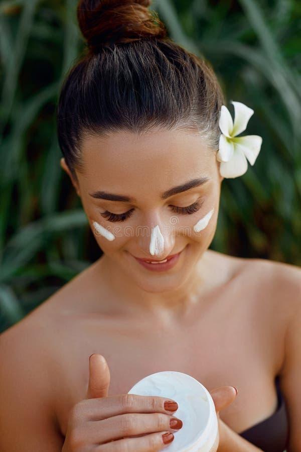 Modello del fronte di bellezza Bella donna con la crema cosmetica della pelle della bottiglia pulita facciale liscia sana della t immagine stock libera da diritti