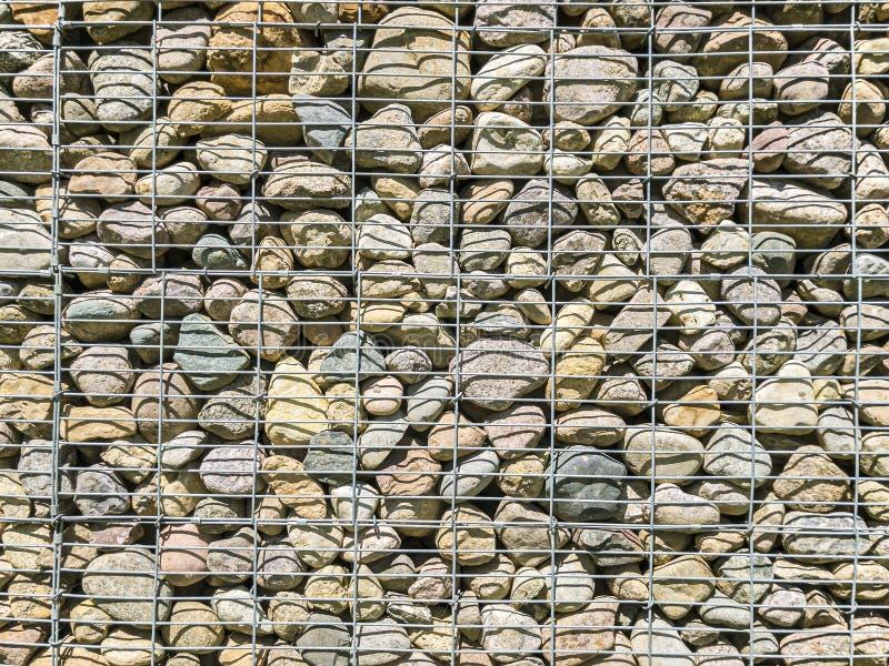 Modello del gabbione griglia del metallo con molte pietre naturali rotonde dentro fotografie stock libere da diritti