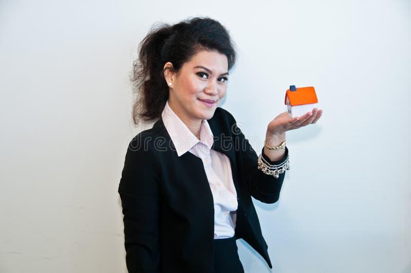Modello del giocattolo della casa della tenuta della donna di affari su fondo bianco immagine stock