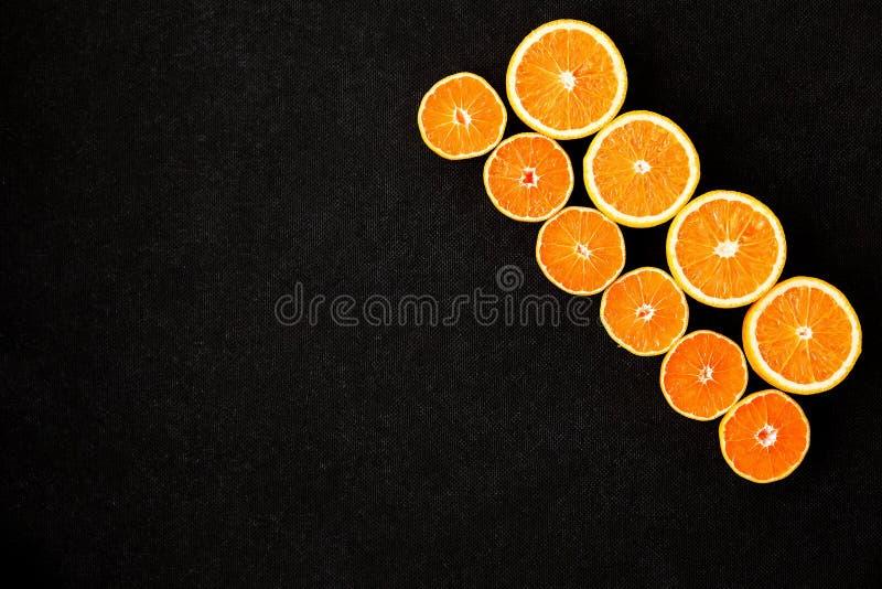 Modello del mandarino e dell'arancia su un fondo nero fotografia stock libera da diritti