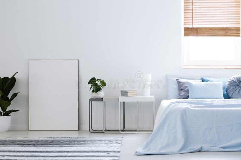 Modello del manifesto vuoto bianco nei wi interni della camera da letto semplice dell'hotel fotografie stock