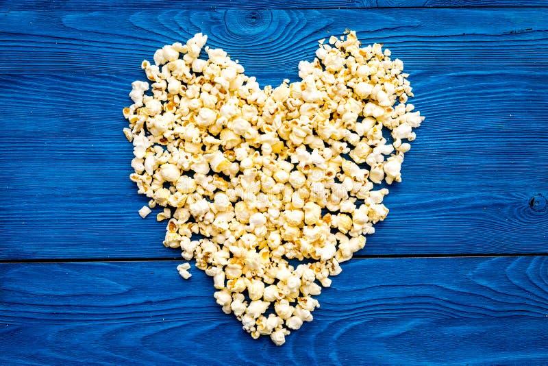 Modello del popcorn sullo spazio blu della copia di vista superiore del fondo Figura del cuore immagini stock