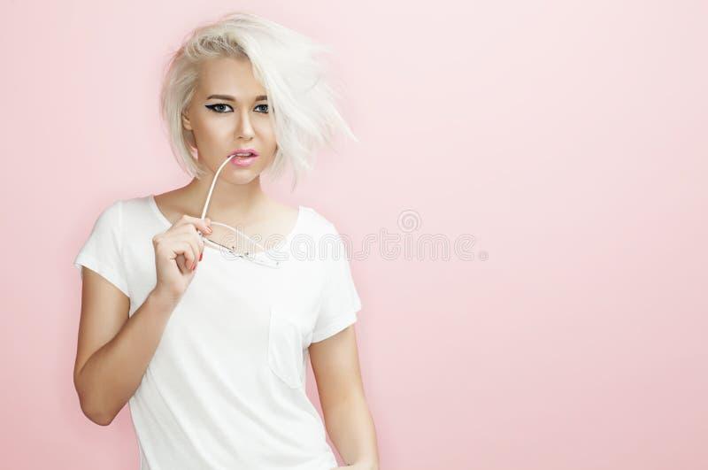 Modello del ritratto con gli occhiali da sole un fondo rosa immagini stock libere da diritti