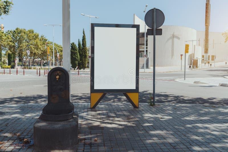 Modello del tabellone per le affissioni della città vicino alla fontanella fotografie stock libere da diritti
