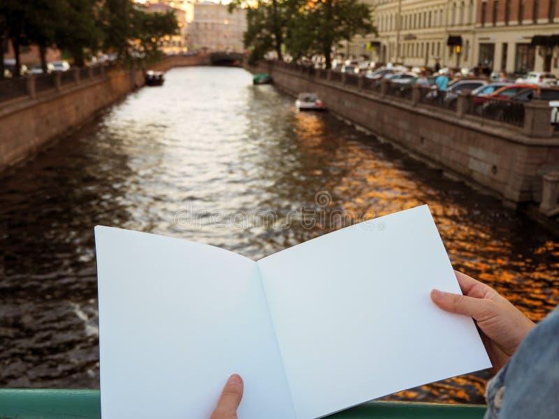 Modello del taccuino in bianco in mani femminili sui precedenti del fiume della città fotografia stock libera da diritti