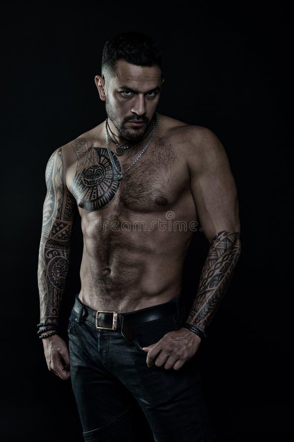 Modello del tatuaggio con gli addominali scolpiti e l'ab Uomo barbuto con il corpo tatuato Uomo con il torso nudo sexy in jeans a immagini stock libere da diritti