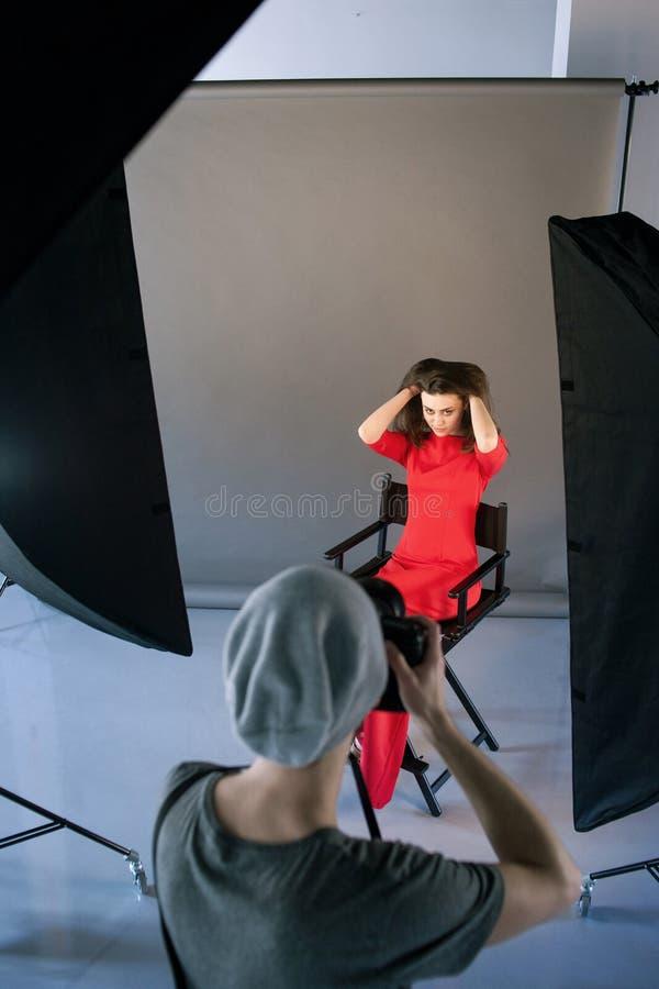 Modello del tiro del fotografo nel rosso alla sessione dello studio immagini stock