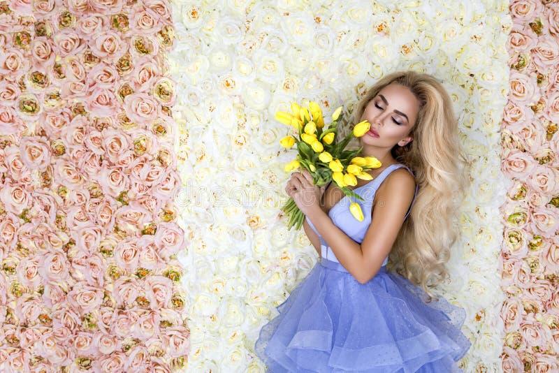 Modello del vestito da sposa da modo con un mazzo dei tulipani Bello modello della sposa in vestito da sposa stupefacente blu Gio fotografie stock