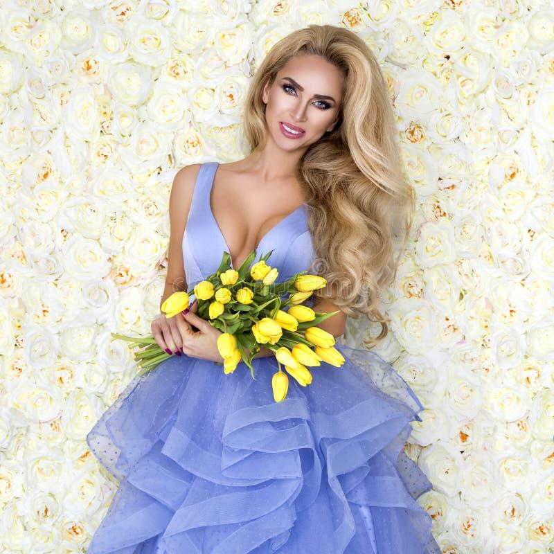 Modello del vestito da sposa da modo con un mazzo dei tulipani Bello modello della sposa in vestito da sposa stupefacente blu Gio fotografia stock
