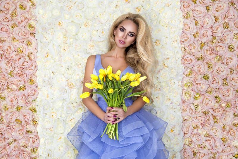 Modello del vestito da sposa da modo con un mazzo dei tulipani Bello modello della sposa in vestito da sposa stupefacente blu Gio fotografie stock libere da diritti