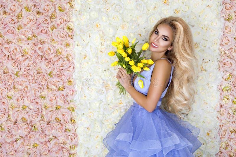 Modello del vestito da sposa da modo con un mazzo dei tulipani Bello modello della sposa in vestito da sposa stupefacente blu Gio fotografia stock libera da diritti