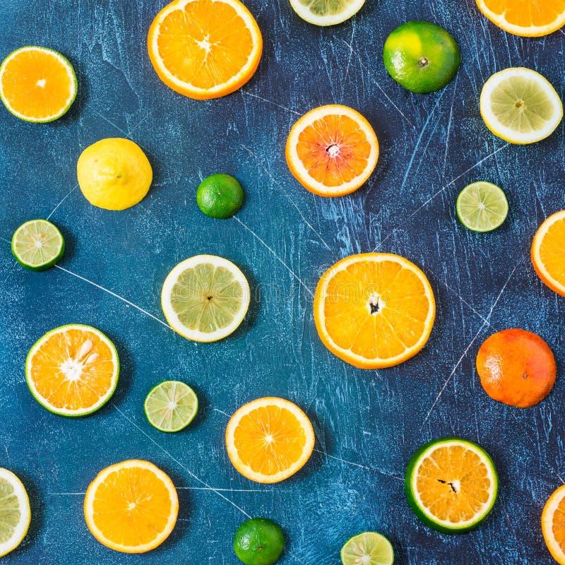 Modello dell'agrume su fondo blu Agrumi Assorted Fette di arancia, mandarino, limone, calce Vista superiore quadrato immagini stock