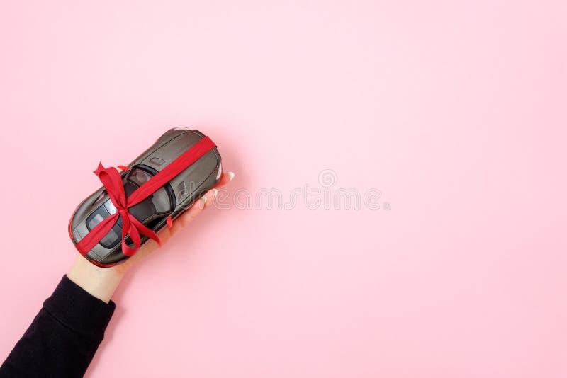 Modello dell'automobile del giocattolo della tenuta della mano della donna legato con un nastro e un arco rossi come regalo su fo immagine stock libera da diritti