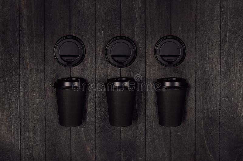 Modello dell'imballaggio del caffè - tazze di carta nere delle FO tre dell'insieme e cappucci in bianco sul bordo di legno nero s fotografia stock