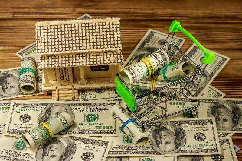Modello della Camera e piccolo carrello con i rotoli dei dollari sul mucchio di U S cento banconote in dollari su fondo di legno immagini stock