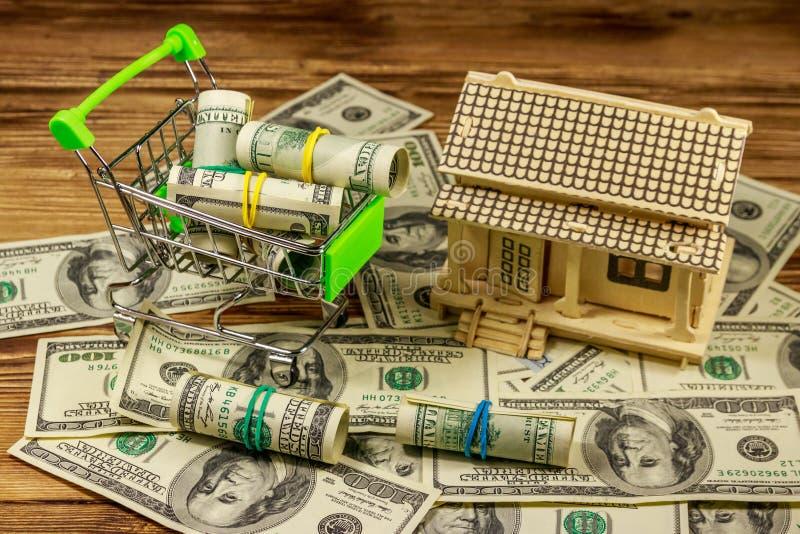 Modello della Camera e piccolo carrello con i rotoli dei dollari sul mucchio di U S cento banconote in dollari su fondo di legno fotografia stock