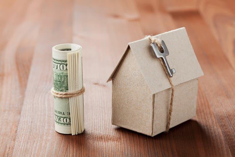 Modello della casa del cartone con la chiave e le banconote in dollari Costruzione della Camera, prestito, bene immobile, costo d fotografia stock libera da diritti
