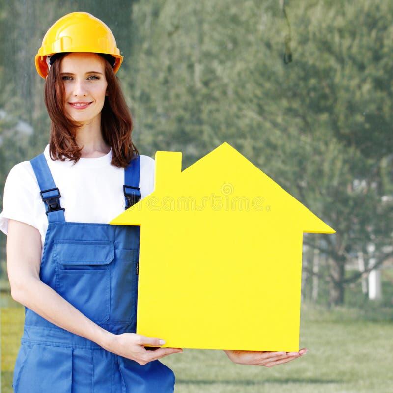 Modello della casa della tenuta del lavoratore immagine stock
