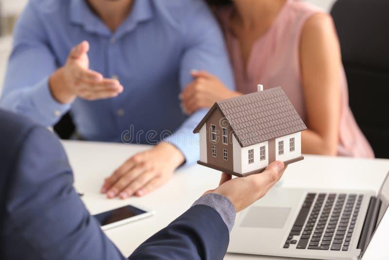 Modello della casa di rappresentazione dell'agente immobiliare ai clienti in ufficio fotografia stock