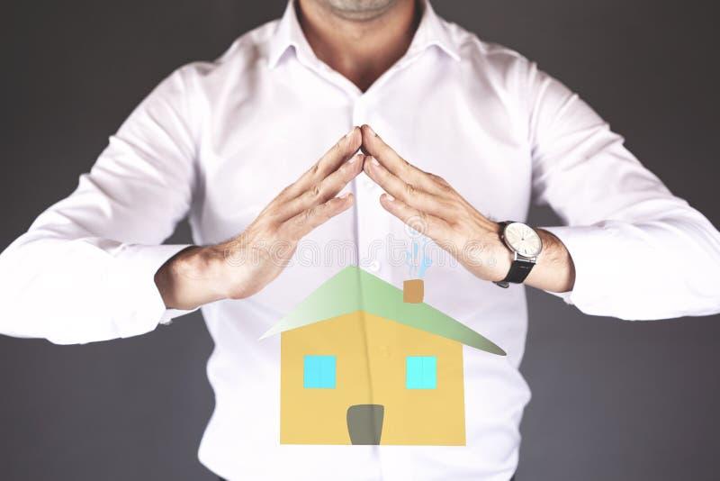 Modello della casa della mano del giovane in schermo immagini stock