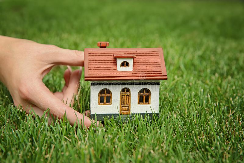 Modello della casa della tenuta della donna su prato inglese verde immagine stock libera da diritti