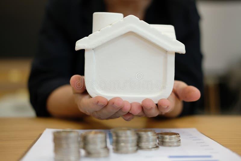 Modello della casa della tenuta della mano le monete impilano & il piano dell'acquisto della proprietà fotografia stock libera da diritti