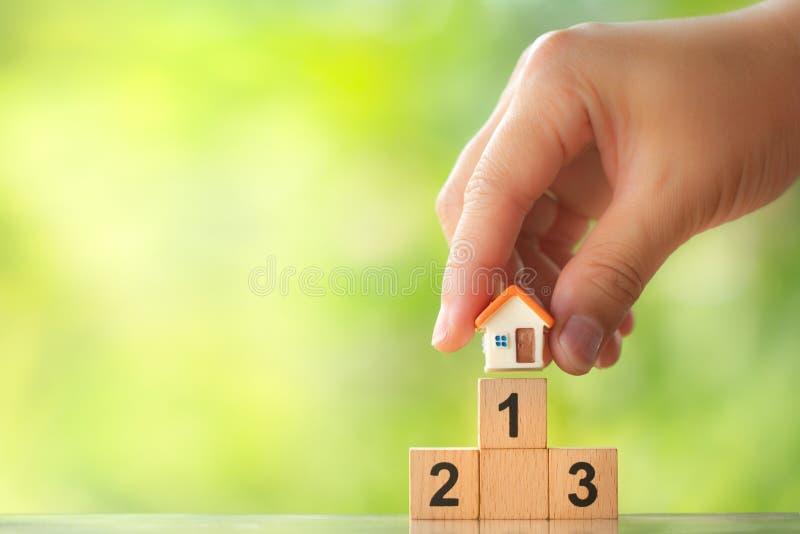 Modello della casa della tenuta della mano sul primo posto del podio del vincitore su fondo vago pianta fotografia stock