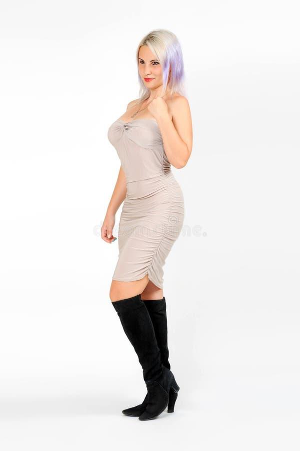 Modello della donna in breve vestito beige ed in stivali neri immagine stock libera da diritti
