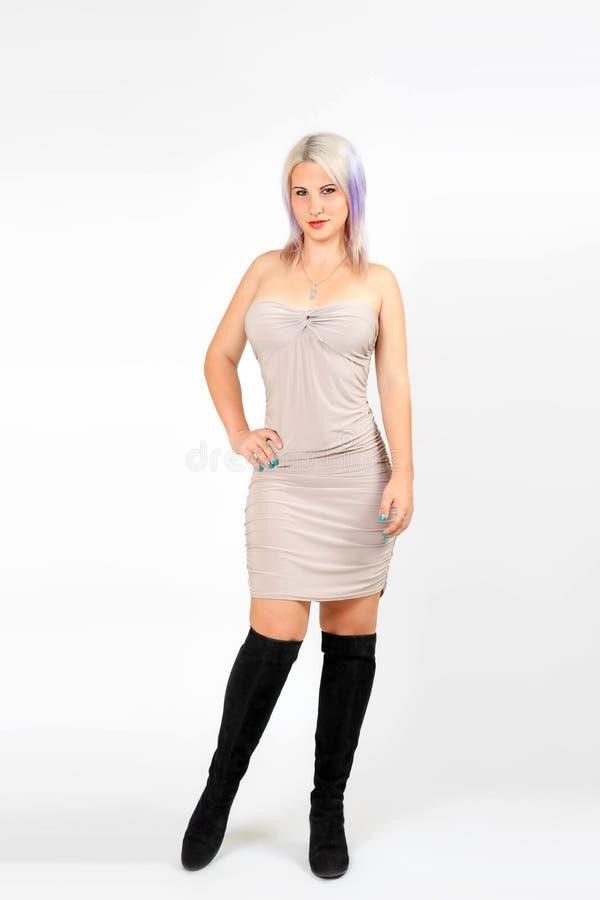 Modello della donna in breve vestito beige ed in stivali neri immagine stock