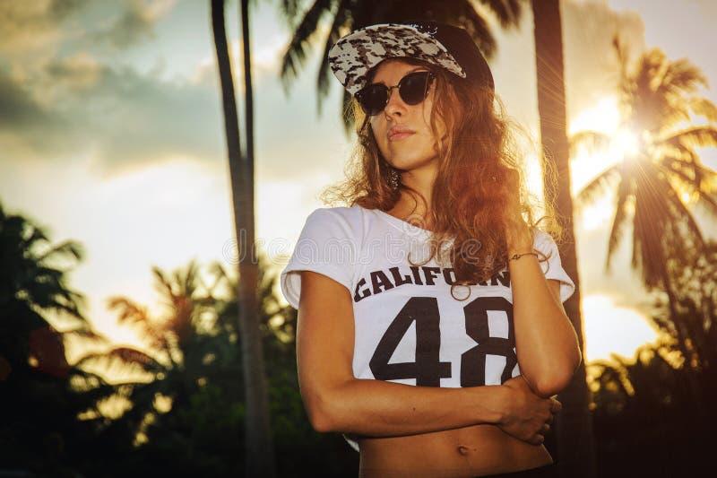 Modello della giovane donna in berretto da baseball ed in occhiali da sole sul backround di tramonto immagine stock