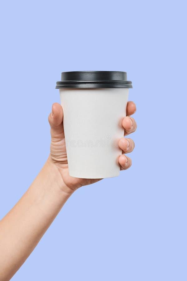 Modello della mano del ` s degli uomini che tiene la tazza di taglia media del Libro Bianco con la copertura nera immagini stock