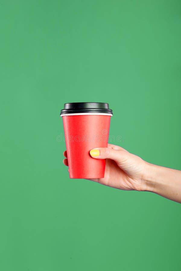 Modello della mano femminile che giudica una tazza di carta del caffè isolata su fondo verde immagini stock