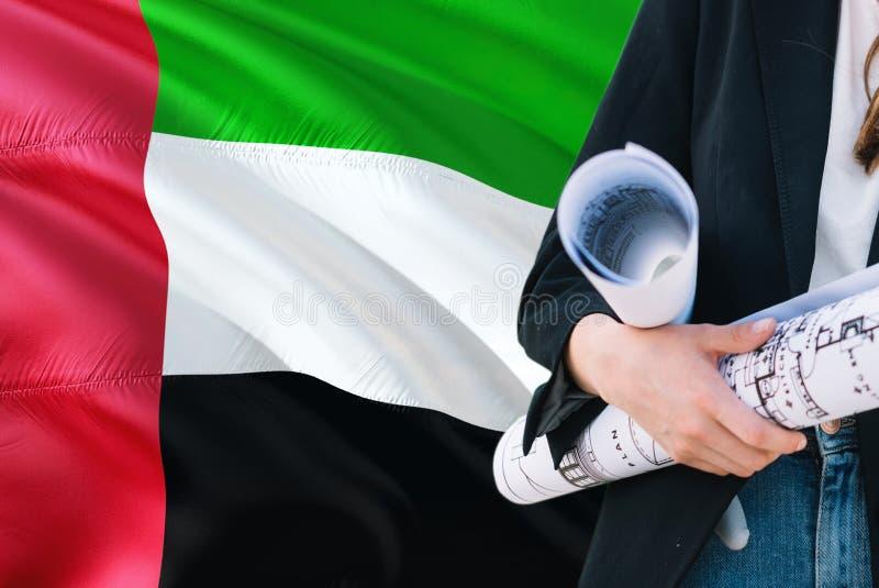 Modello della tenuta della donna dell'architetto contro gli Emirati Arabi Uniti che ondeggiano il fondo della bandiera Concetto d fotografia stock libera da diritti