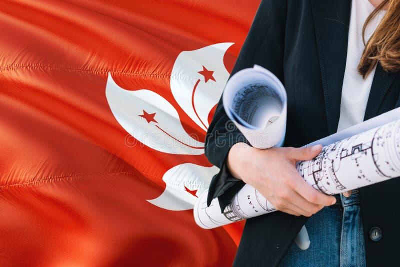 Modello della tenuta della donna dell'architetto contro il fondo d'ondeggiamento della bandiera di Hong Kong Concetto di architet immagini stock