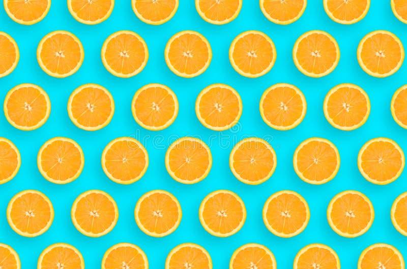 Modello delle fette arancio di un agrume su fondo blu luminoso fotografie stock libere da diritti