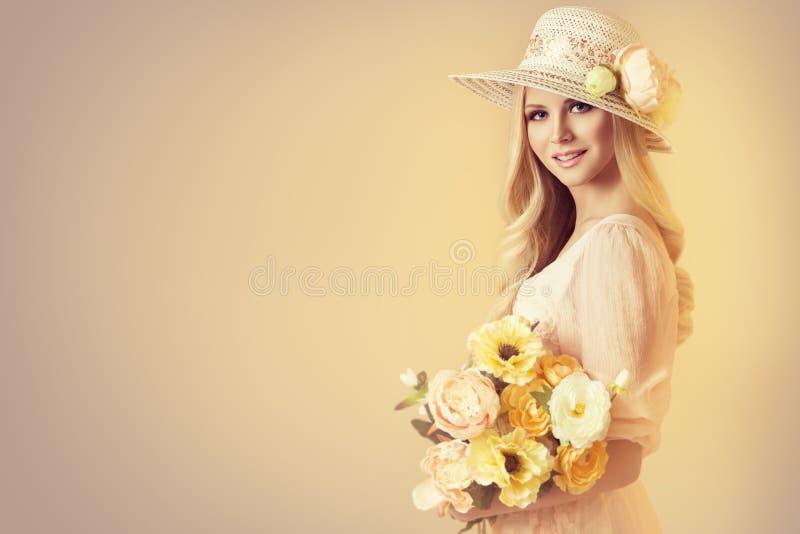 Modello di bellezza in vasti cappello del bordo di modo, donna e fiori della peonia immagini stock