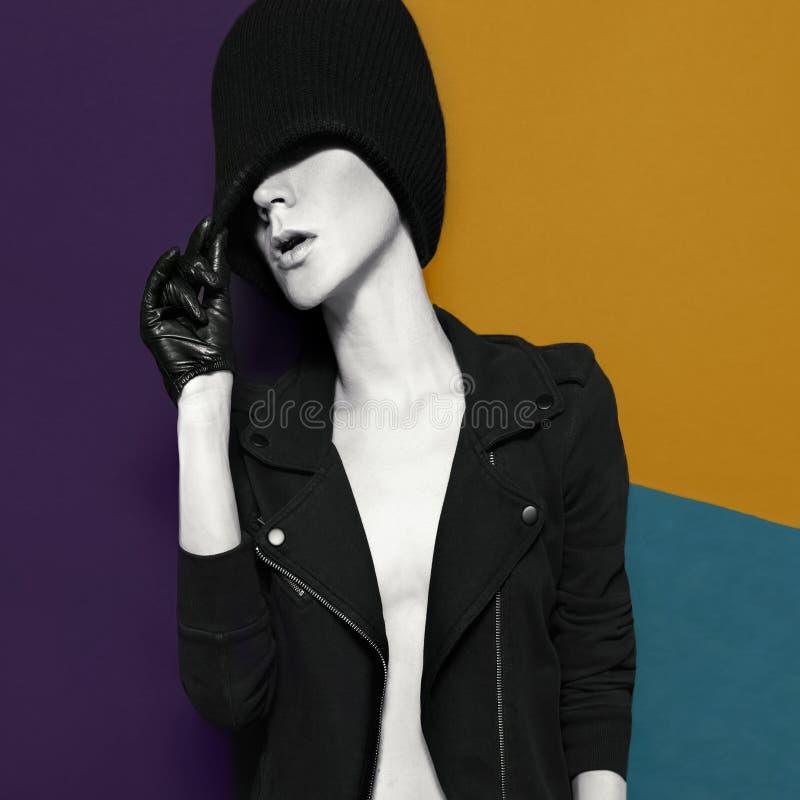 Modello di fascino in guanti di cuoio alla moda e cappello sull'sedere variopinte fotografie stock